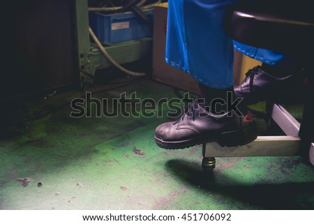 Old safety shoes black color on the green concrete floor.