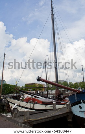 Old sailing boats on a dock in Amsterdam, in summer 2010. - stock photo