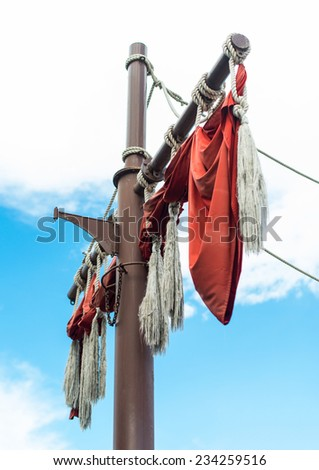 Old sailing ship masts with red sails. - stock photo