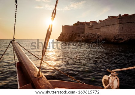 Old sailing ship sails into the sunset next to the city walls of Dubrovnik - stock photo