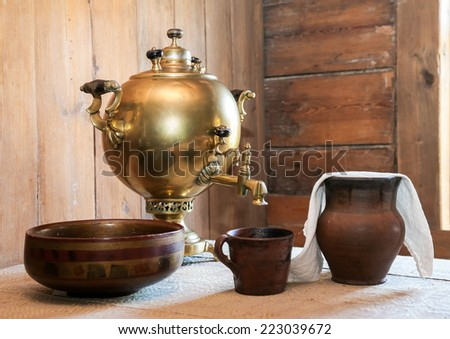 Old samovar and ceramic dishes on a table in a country house - stock photo
