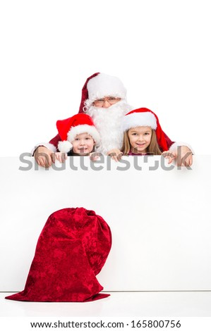 Old Santa Claus and two little kids standing behind white blank poster. Red Santa sac on foreground isolated over white background  - stock photo