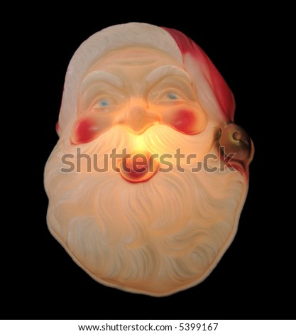 old Santa Claus decoration lit up and isolated on black - stock photo