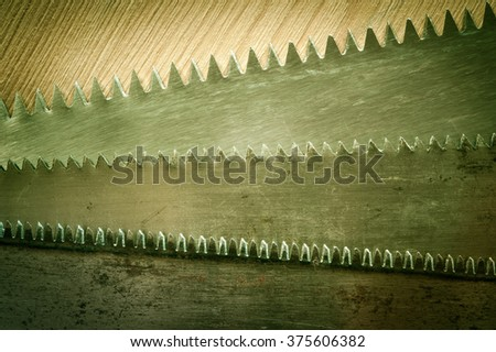 Old saws blade on the wooden background. Toned.