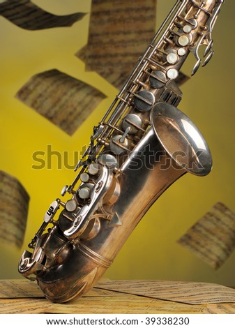 Old saxophone and flying musical notes on a background. The Musical instrument standing on notes with classical music of the beginning of 17 centuries - stock photo