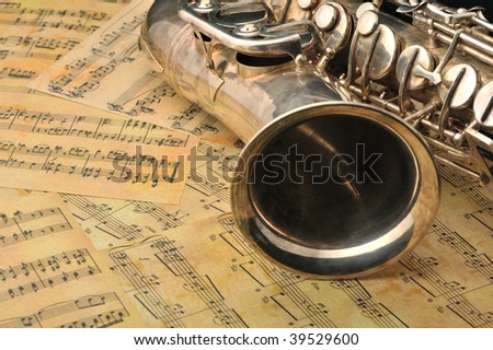 Old saxophone and notes. The Musical instrument laying on notes with classical music of the beginning of 17 centuries - stock photo
