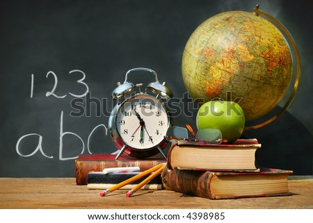 Old school books on a desk with atlas - stock photo