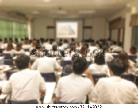 Old school day vintage style blurred abstract background of university undergraduate students studying in a classroom: Blurry view of college school from back of the lecture room with projector screen - stock photo