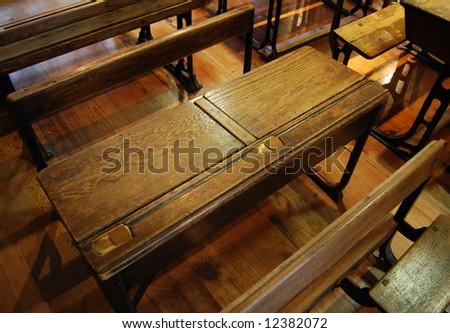 Old school desks inside of classroom - stock photo