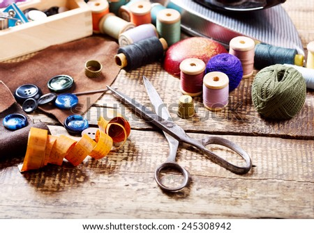old  scissors, various threads  and sewing tools on wooden table - stock photo