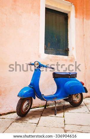 Old scooter leaning against a wall in Italy - stock photo