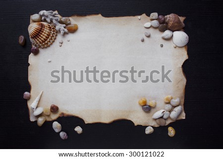 Old scroll of parchment with sea pebbles and seashells, nautical theme, place for text - stock photo