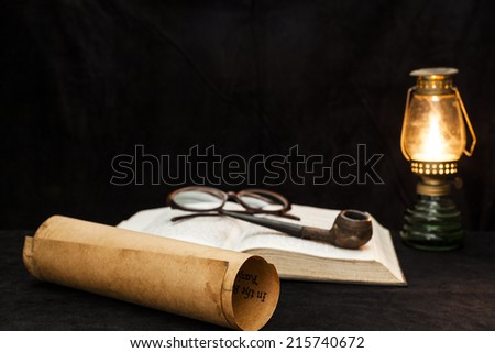 Old scroll with bible glasses and a pipe in fire lamp light