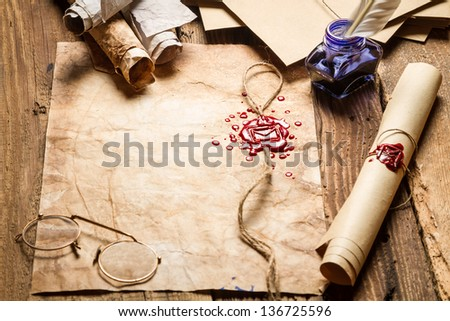Old scrolls with red sealant, glasses and blue ink in the inkwell - stock photo