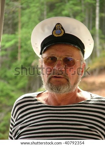 Old seaman with a white hat and stripy shirt - stock photo