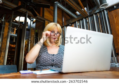 Old senior business woman with surprise emotion on face and big eyes, looking to computer laptop sitting in summer cafe place - stock photo