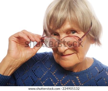 old senior lady looking through her eyeglasses isolated on white background - stock photo