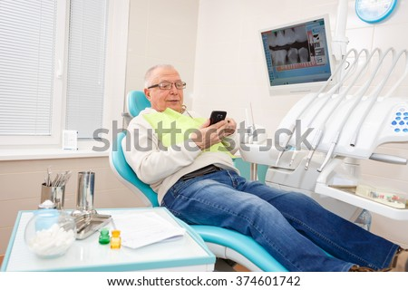 Old senior man sitting in a chair in dental clinic read or write sms on cell mobile phone. - stock photo