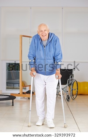 Old senior man walking with crutches in physiotherapy - stock photo