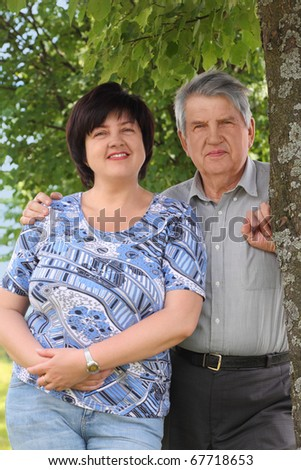 old senior standing near tree and embracing his adult daughter, smiling, summer