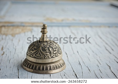 Old service bell resting on weathered wooden surface with blue peeling paint - stock photo