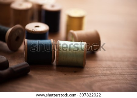 Old sew thread wooden reels or bobbins on a old grungy work table. Tailor's work table. textile or fine cloth making. Shallow depth of field. - stock photo