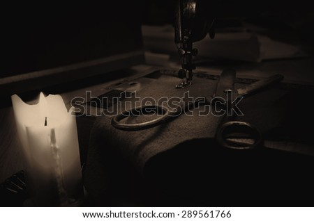 old sewing machine, fabric and rusty scissors at the light candle. horizontal, sepia, low key - stock photo