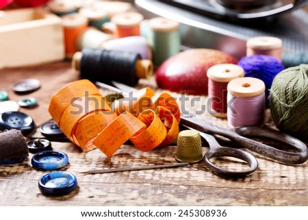 old sewing tools on wooden table - stock photo