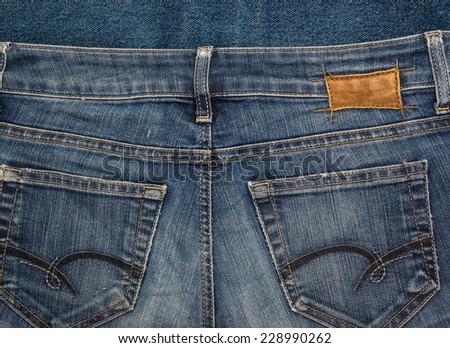Old shabby indian blue denim jeans pants with pockets and metal rivets. Background for fashion design and identity - stock photo