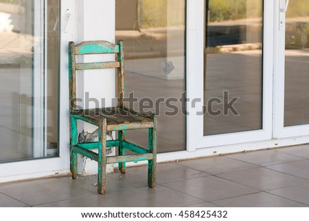 Old shabby wooden turquoise chair on the background of the glass doors with white frames