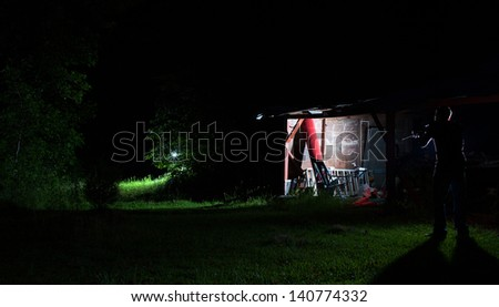 Old shed in disrepair with a man walking by with a gun - stock photo
