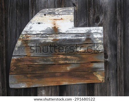 Old ship rudder nailed to the side of a barn. - stock photo
