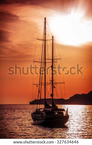 Old ship sailing to the sunset. Dramatic dark evening sea view - stock photo