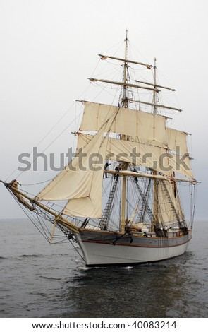 Old ship with white sales in the baltic sea - stock photo