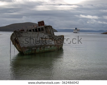 Old ship wreck at shore with a cruise ship in the background at New Island Falkland Islands