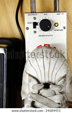 Old shoe pushing a guitar rusty pedal. - stock photo
