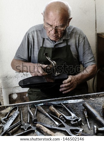 Old shoemaker repair the sole of a shoe. - stock photo