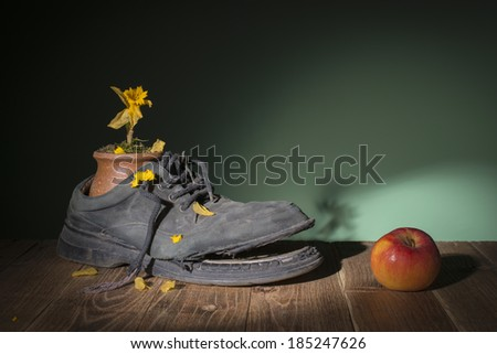 Old shoes and dried flowers in a ceramic vase - stock photo
