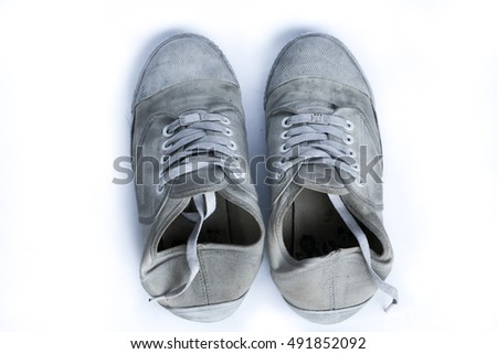 Old shoes on the white background, black and dirty shoes and smell not good