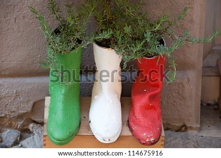 old shoes processed on flowerpots - stock photo