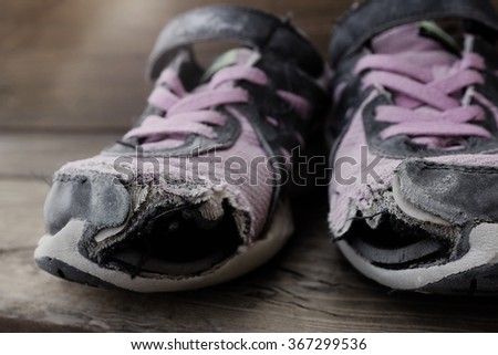 Old shoes with holes worn down shabby for homeless clothing - stock photo