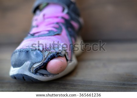 Old shoes with holes worn down shabby for homeless clothing toes sticking out - stock photo
