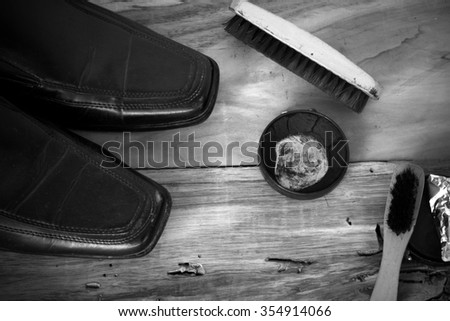 old shoes with shoe polish and shoe brush on wood processed with black ans white style