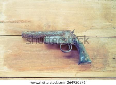 Old short gun on the wooden board , rusty hand gun - stock photo