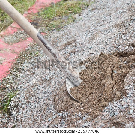 Old shovel dig in pile of sand - stock photo