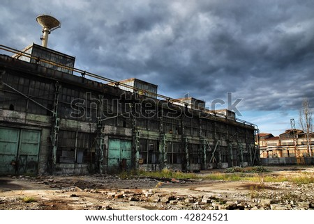 Old shut down factory is overshadowed by dark stormy clouds - stock photo