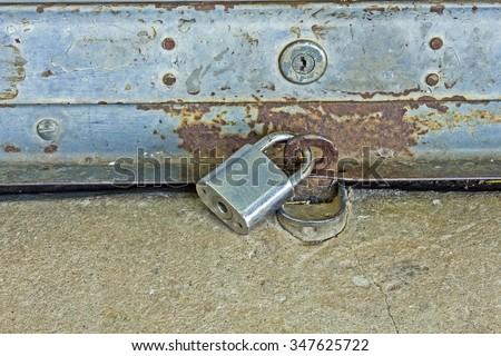 old shutter door with hasp - Key lock pad of roller shutter door - stock photo
