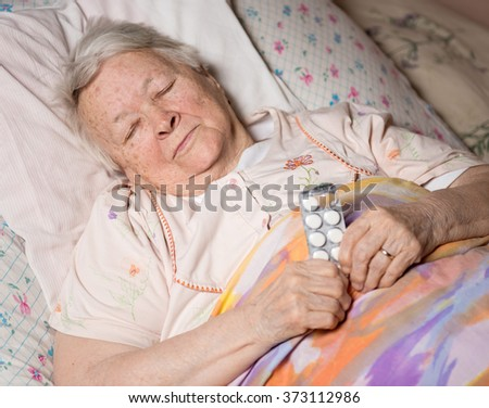 Old sick woman lying at bed, holding the medicine in hands - stock photo