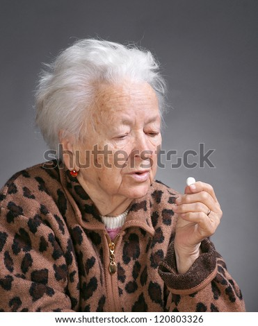Old sick woman with pills on a gray background