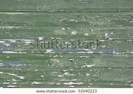 Old siding with peeling green paint - stock photo